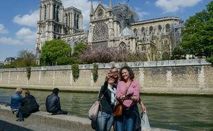 Des touristes se prennent en photo devant Notre-Dame, le 17 avril 2019.