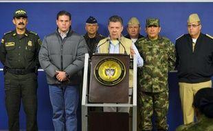 Le président colombien Juan Manuel Santos (c), lors d'une conférence de presse, le 16 novembre 2014 à Bogota, après l'enlèvement d'un général de l'armée