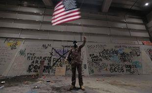 Un homme brandit un drapeau américain lors d'une manifestation devant la Cour de Justice de Portland.
