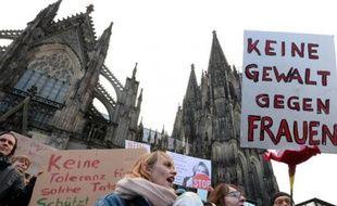 """Un homme tient une pancarte """"pas de violence contre les femmes"""" lors d'une manifestation devant la cathédrale de Cologne le 9 janvier 2015"""