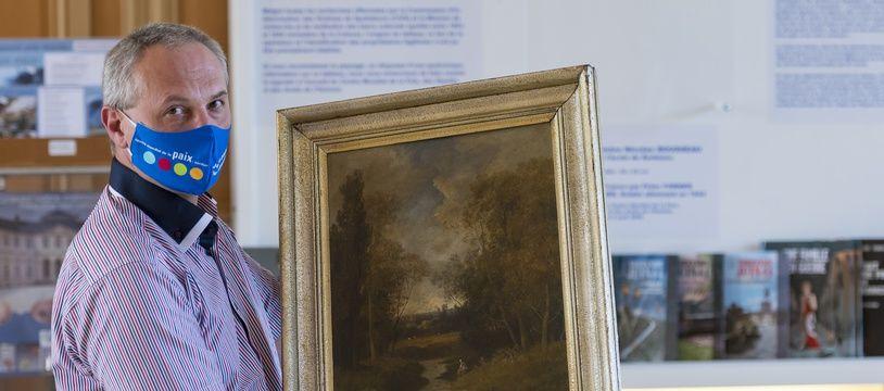 Philippe Hansch, directeur du Centre mondial de la paix de Verdun, présente le tableau de Nicolas Rousseau dérobé sous l'Occupation