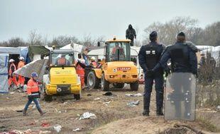 """Des policiers surveillent le démantèlement d'abris dans la """"jungle"""" de Calais par des bulldozers, le 1er mars 2016"""