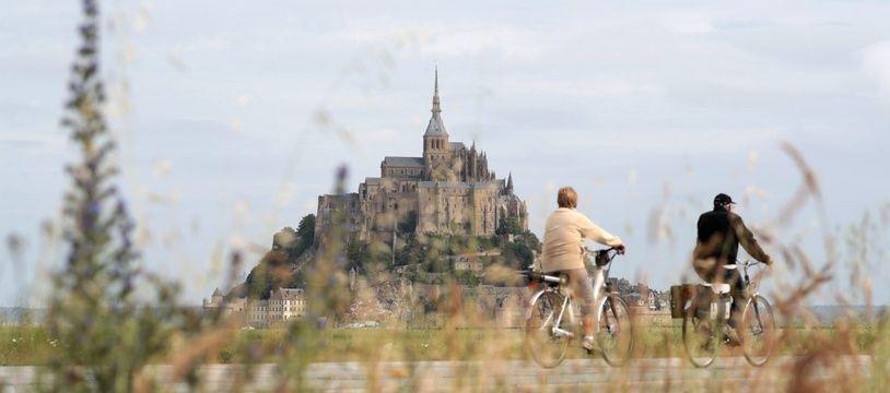 Un couple de cyclotouristes arrive au Mont-Saint-Michel, le 24 juillet 2016.