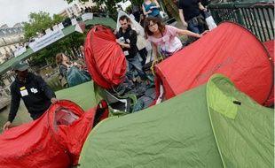 Des membres d'associations d'aide aux sans-abris montent des tentes quai de Valmy à Paris le 9 juin 2014