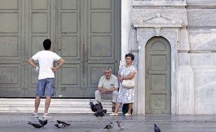 Des gens attendent devant les portes closes de la Banque nationale de Grèce à Athènes, le 8 juillet 2015.