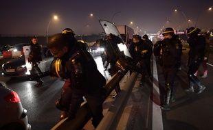 Des CRS interviennent alors que des chauffeurs de VTC en grève bloquent l'autoroute menant à l'aéroport d'Orly, le 17 décembre 2016. AFP PHOTO / Christophe ARCHAMBAULT