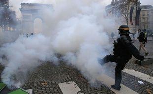 Paris, le 24 novembre 2018. Un policier donne un coup de pied pour envoyer une grenade vers des personnes mobilisées dans le cadre du mouvement des «gilets jaunes».