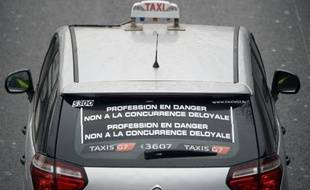 """Un taxi affiche sur sa vitre arrière """"Profession en danger. Non à la concurrence déloyale"""", le 15 décembre 2014 à Paris"""