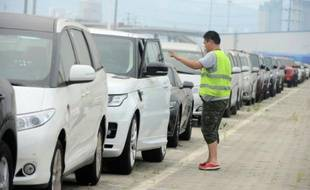 Un homme vérifie des voitures importées à Qingdao le 19 août 2015