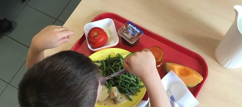 Un petit garçon attablé à une table de la cantine de l'école François-Mitterand, à Montpellier.