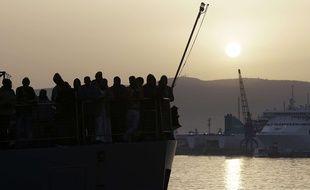 Des migrants attendent de débarquer d'un cargo islandais dans le sud de l'Italie, le 6 mai 2015.