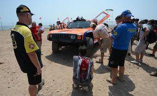 La voiture de l'Américain Robby Gordon scrutée par des mécanos des autres équipes, le 4 janvier 2013, à Lima (Pérou).