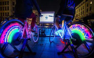 Illustration d'une séance de vélo-cinéma où le public doit pédaler pour voir le film.