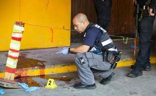 Un policier israélien inspecte les lieux où deux hommes ont été tués le 19 novembre 2015 dans une attaque anti-israélienne, à Tel-Aviv
