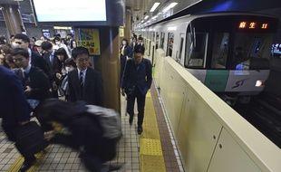 Des passagers attendant le train sur le quai d'une gare japonaise. Illustration.