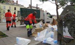 Des agents du nettoiement ramassent des détritus au sol quartier Bouffay.