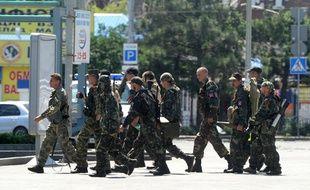 Des séparatistes armés prorusses traversent une rue à proximité de la gare de Donetsk ce lundi 21 juillet alors que des tirs d'artillerie secouent le quartier.