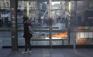 Des tags de la ZAD sur un abribus devant une poubelle en feu, le 14 avril en centre-ville de Nantes.
