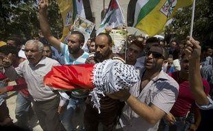 Des Palestiniens portent le corps du petit Ali Dawabcheh, 18 mois, brûlé vif dans l'incendie de la maison familiale imputé à des extrémistes juifs, le 31 juillet 2015.