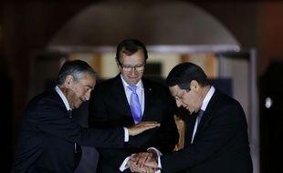 Les dirigeants chypriotes Mustafa Akinci (à g.) et Nicos Anastasiades (à dr.), réunis par l'envoyé spécial de l'ONU Espen Barth Eide, le 11 mai 2015.