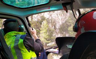 A  bord d'un hélicoptère, le géologue de la métropole Nice Côte d'Azur inspecte les parois surplombant la route de la Vésubie