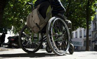 Une personne en fauteuil roulant participe à une manifestation pour demander plus d'accessibilité, devant l'Assemblée nationale, le 06 juillet 2015 à Paris