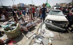 Des passants constatent les dégâts après l'explosion d'une voiture piégée près d'un marché du grand quartier chiite Sadr City, dans le nord de Bagdad le 11 mai 2016