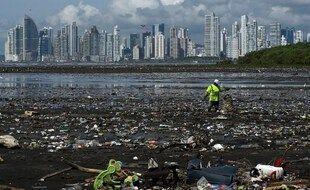 Un homme ramasse des ordures, y compris des déchets plastiques, sur la plage de la Costa del Este, à Panama City, le 19 avril 2021.