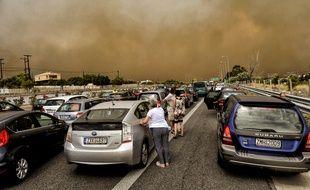 Les voitures sont bloquées à la route nationale fermée pendant un feu de forêt à Kineta, près d'Athènes, le 23 juillet 2018.