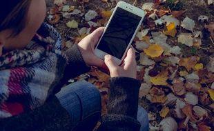 Une adolescente consultant son smartphone.