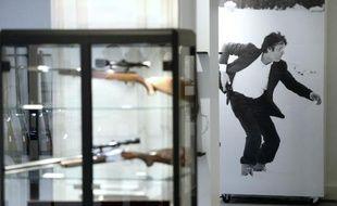 Des armes appartenant à Alain Delon exposées devant une affiche de l'acteur le 28 novembre 2014 à la maison Cornette de Saint Cyr à Paris