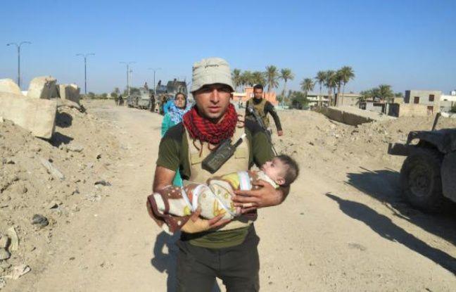 Les forces de sécurité irakiennes évacuent des civils alors qu'ils dégagent le quartier de Sufia près de Ramadi le 14 janvier 2016