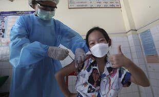 Une jeune cambodgienne reçoit une injection du vaccin COVID-19 de Sinovac dans un centre de santé de Samrong Krom à l'extérieur de Phnom Penh, au Cambodge, le vendredi 17 septembre 2021.