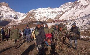 Un randonneur blessé transporté par des soldats népalais dans le district de Manang, près du trekking du tour des Annapurnas, le 15 octobre 2014 dans l'Himalaya