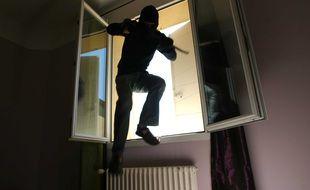Illustration d'un cambrioleur qui s'introduit dans un appartement par une fenêtre ouverte.