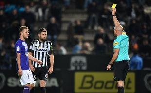 L'arbitre Bartolomeu Varela donne un carton jaune au Toulousain Alexis Blin (à gauche) et à l'Angevin Thomas Mangani lors du match de Ligue 1 à Angers, le 22 octobre 2016.
