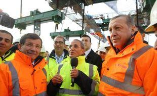 Une photo fournie par le service de presse du Premier ministre turc le 6 mars 2016 montre le président Recep Tayyip Erdogan (d) et son Premier ministre Ahmet Davutoglu (g) lors d'une cérémonie sur le pont en contruction Yavuz Sultan Selim à Istanbul
