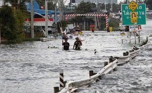 Des Thaïlandais marchent dans une rue inondée de Bangkok, le 25 octobre 2011.