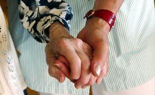 Une aide-soignante tient la main d'une personne âgée