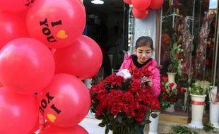 Une jeune Syrienne arrange des fleurs dans un magasin, pour la Saint-Valentin dans la ville de Qamishli (Nord-Est de la Syrie), le 13 février 2016