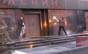 Capture d'écran d'une vidéo diffusée sur YouTube monrtant deux Russes,  Evgueni Avilov et Oleg Bassov, asperger le mausolée de Lénine d'eau bénite à Moscou.