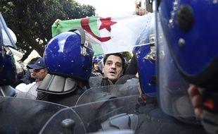 Un des nombreux manifestants ce dimanche 24 février à Alger entouré par un important dispositif policier.