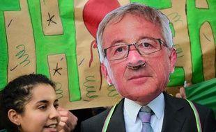 Un militant opposé au Partenariat transatlantique de commerce et d'investissement (TTIP) manifeste devant la Commission européenne à Bruxelle le 9 décembre 2014, un masque du président de la Commission européenne Jean-Claude Juncker sur le visage