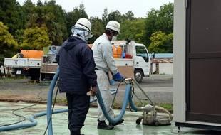 Deux employés travaillent à la décontamination d'un site dans la ville de Naraha, à l'intérieur de la zone d'exclusion autour de la centrale de Fukushima, le 13 juin 2013.