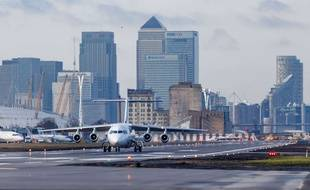 A Cityjet airliner taxying along the London City Airport runway with the backdrop of Canary Wharf and the O2 Arena, London, UK Various