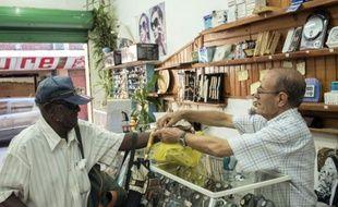 Aboud Ellias (D), né en Syrie et ancien professeur d'arabe, sert un client, le 29 septembre 2015, dans son magasin de Fort-de-France, où il vit depuis 1978