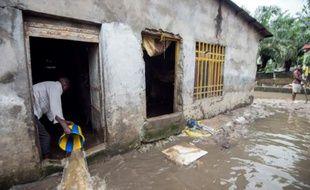 Un homme vide l'eau qui inonde sa maison à Limete, à Kinshasa, le 9 décembre 2015