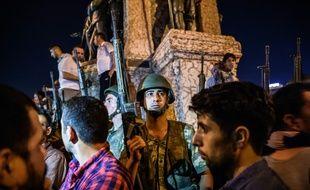 Des soldats turcs en armes sur la place Taksim alors que des personnes protestent contre la tentative de coup d'Etat, à Istanbul, en Turquie, le 16 juillet 2016