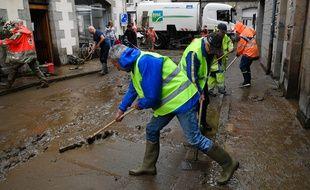Des habitants de Morlaix nettoient la boue déversée dans la rue après de violents orages. Le 4 mai 2018.