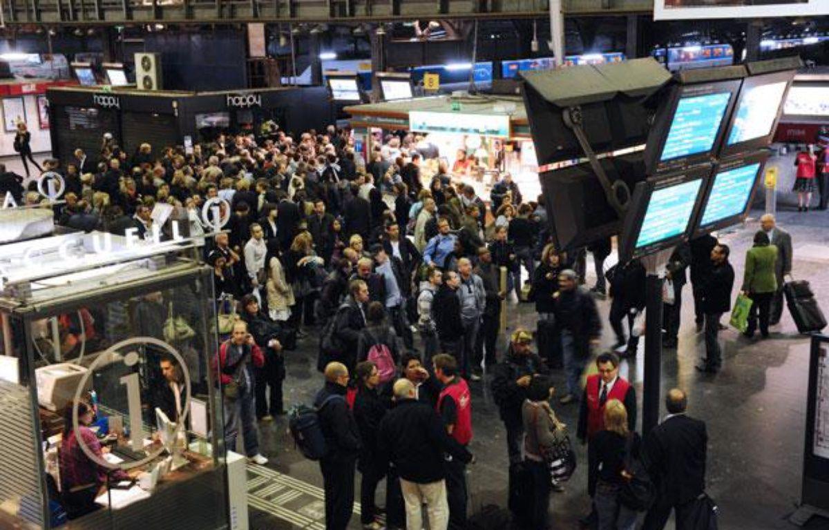 Des usagers de la SNCF rassemblés devant des écrans d'informations, à la gare  de l'Est à Paris, alors qu'un mouvement de grève des cheminots a été déclenché à  la suite de l'agression d'un contrôleur, le 6 octobre 2011. – AFP PHOTO / MIGUEL MEDINA